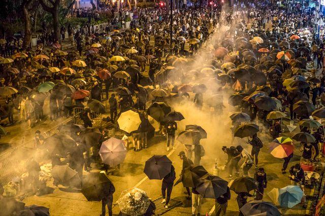 Des manifestants reçoivent du gaz lacrymogène après avoir tenté de pénétrer dans l'enceinte de PolyU pour venir en aide aux manifestants du campus