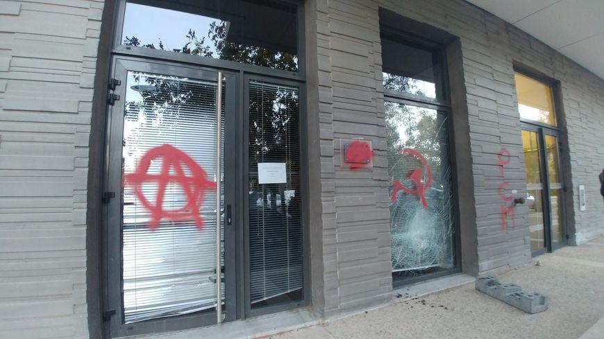 Des tags anarchistes ont été inscrits à la peinture rouge et une vitre a été brisée.