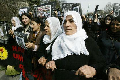 Des femmes kurdes turques tiennent des affiches et portent des photos du massacre de Halabja lors de la manifestation devant l'Université d'Istanbul le 16 mars 2004 pour commémorer le gazage de 5 000 Kurdes par le régime de Saddam Hussein en 1998