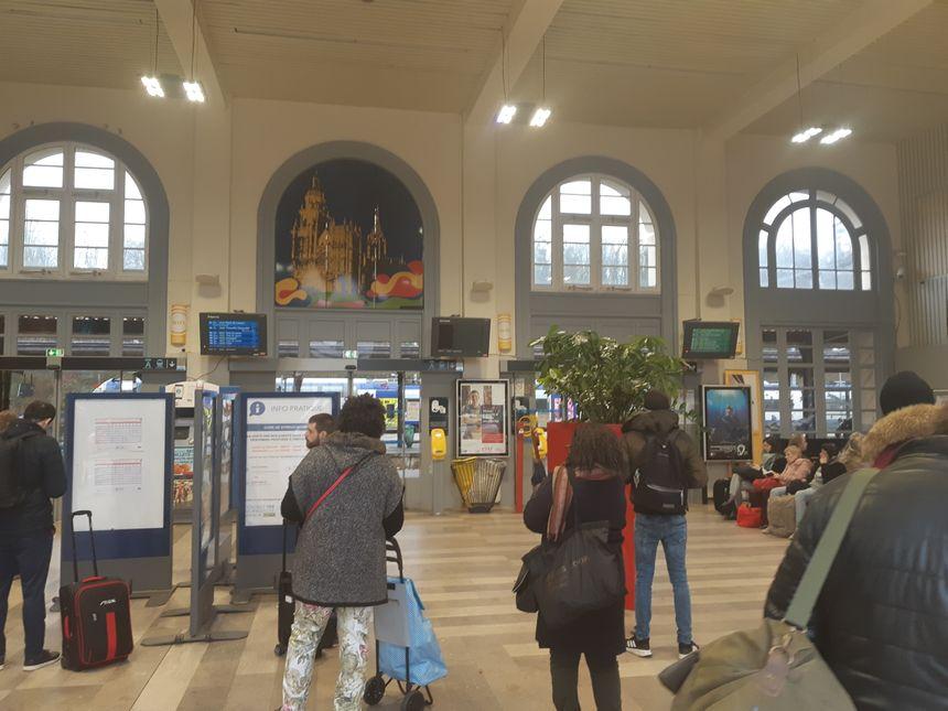 Dans le hall de la gare d'Évreux,  les voyageurs patientent,  il n'y a que la chenille qui part toujours à l'heure
