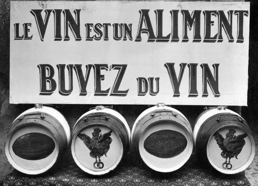 """Photo de 1930 d'une publicité pour le vin """"Le vin est un aliment, buvez du vin"""", prise en marge du tournoi des cinq nations de rugby."""