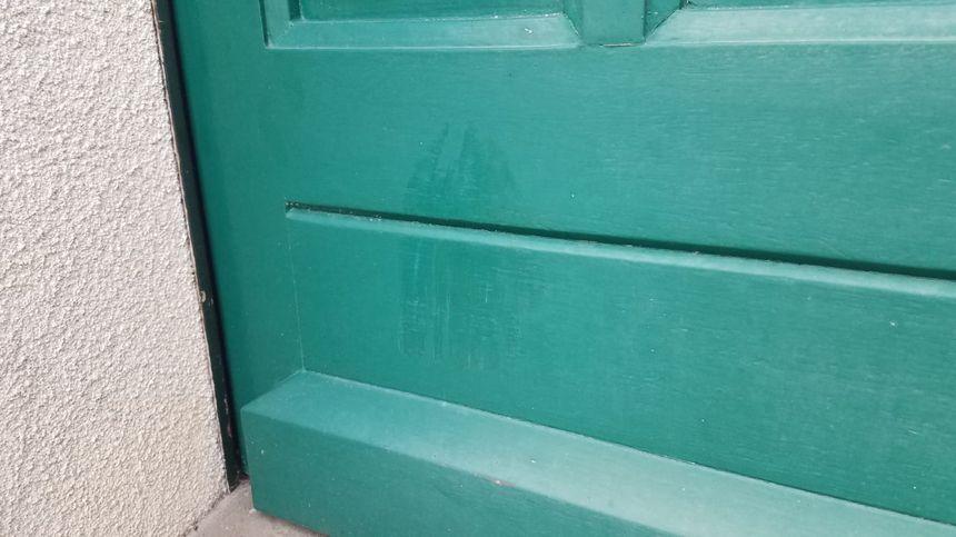 Il reste une trace de bottes de policier sur le bas de la porte d'entrée de la maison de Colette et Jacky.