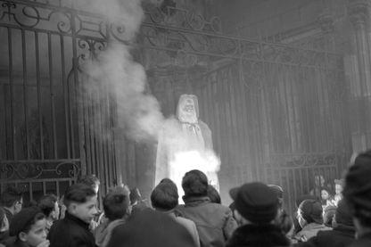 """Désireux de lutter contre """"la fabulation trompeuse"""" du père Noël, symbole du paganisme, le clergé dijonnais fait brûler une représentation de ce dernier devant 250 enfants, le 24 décembre 1951."""