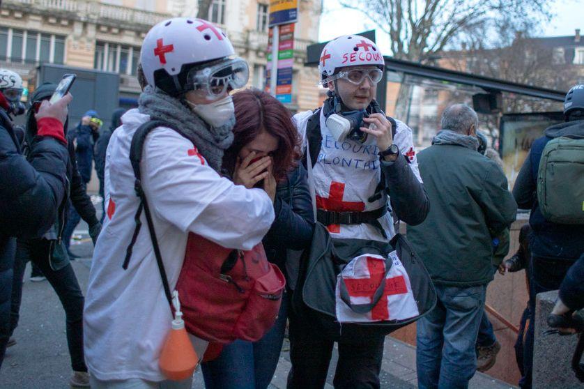 """Des """"street medics"""" accompagnent une manifestante touchée par des gaz lacrymogènes, lors de manifestations à Toulouse."""