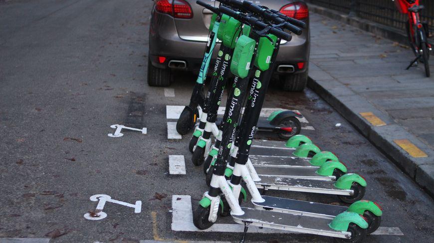 Des trottinettes électriques bien garées à Paris dans un emplacement à cet effet.