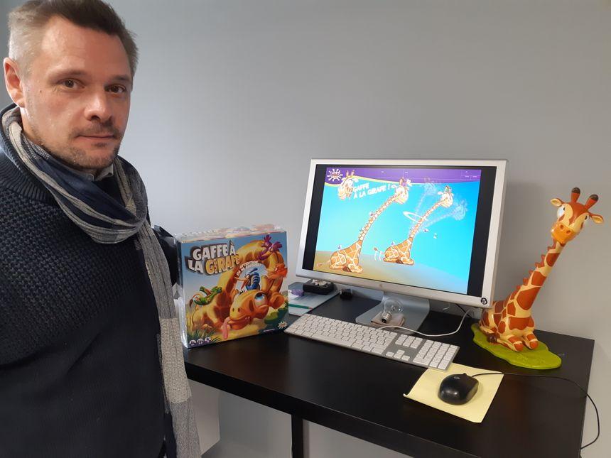 Le directeur de création, David Fromentin, à sa table de travail. Sur l'ordinateur, le premier dessin de la girafe, à droite le prototype et à gauche le jouet dans sa boîte