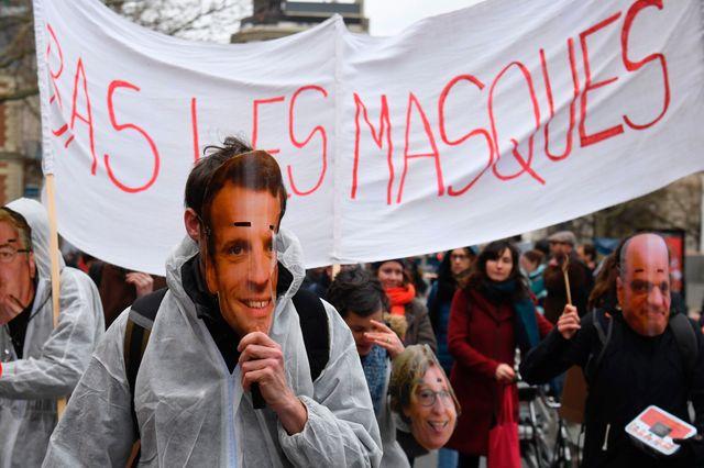 """""""Bas les masques"""" scandent les manifestants qui portent des visages d'Emmanuel Macron et Jean-Michel Blanquer."""