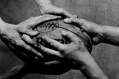 Three men with hands around rugby ball, close-up (B&W) -