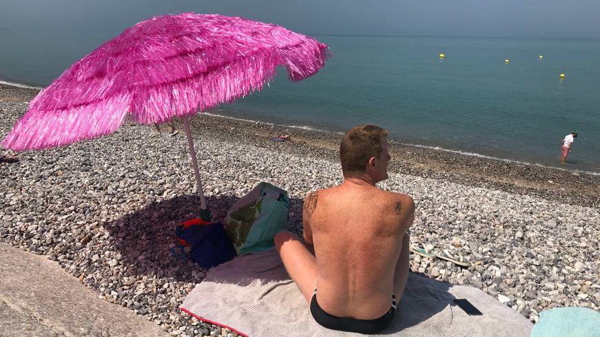 Un homme profite du soleil pendant la canicule sur la plage des Petites-Dalles en Normandie
