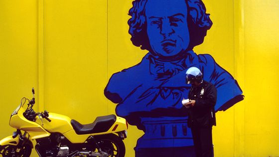 Policeman writing a ticket for an illegally parked motorcycle in downtown Manhattan, in front of a mural of Beethoven.