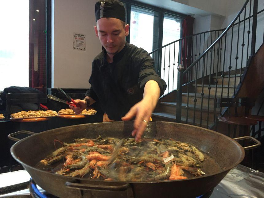 Pendant ce temps, Céleste, cuisinier au restaurant Bodega Bodega, prépare la paella.