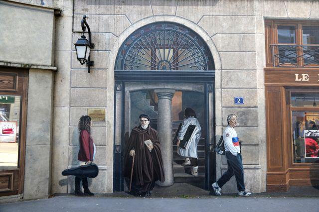 Bernard Lacombe peint sur la fresque des Lyonnais, à droite de l'Abbé Pierre