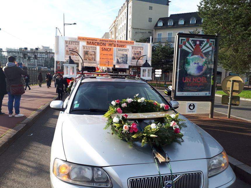 Corbillard et couronne de fleurs en tête du cortége funèbre organisé par les cheminots