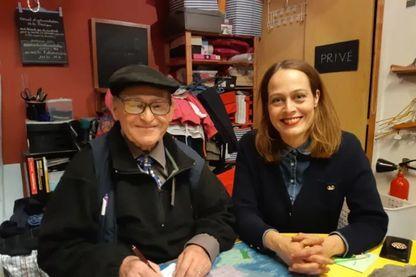 """Julie Hebting, directrice et un bénévole derrière leur bureau de la """"Boutique sans argent"""""""