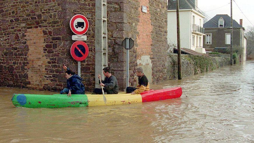 Des riverains circulent en barque, le 28 décembre 1999 dans les rues de Montfort-sur-Meu envahies par les eaux de la rivière le Meu, sortie de son lit durant la tempête.