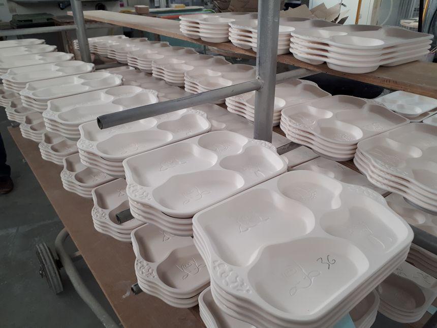 Des dizaines de plateaux repas en porcelaine, prêts pour la cuisson, dans l'usine La Fabrique à Saint-Brice-sur-Vienne.