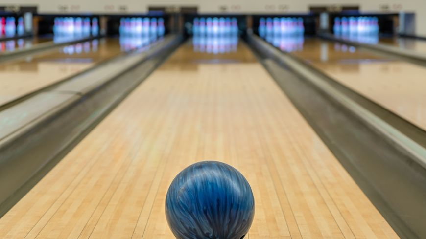 Blue bowling ball on the track in the bowling center