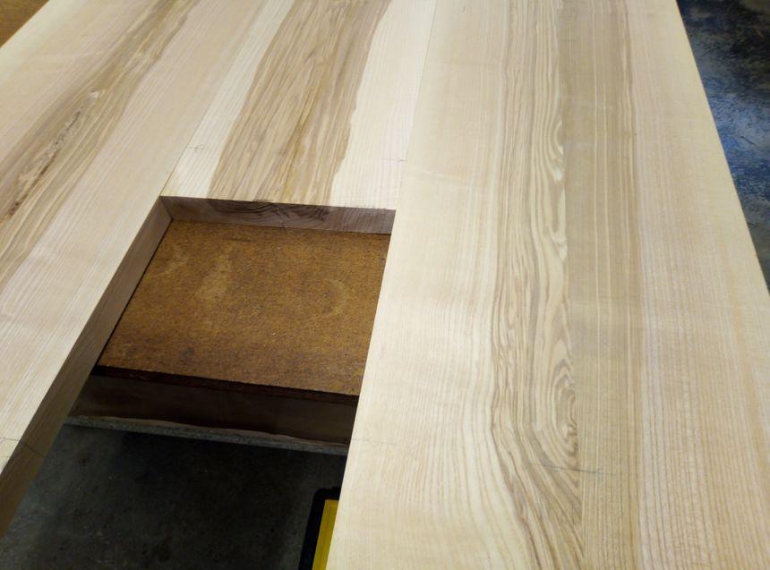 Construction d'une table en frêne-olivier, une essence qui laisse voir des veinures d'olivier.