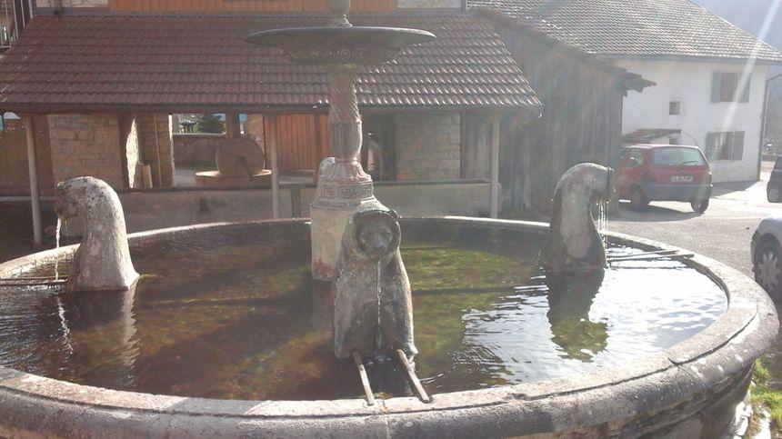 La fontaine aux lions, et l'ancien pressoir à cidre à l'arrière plan