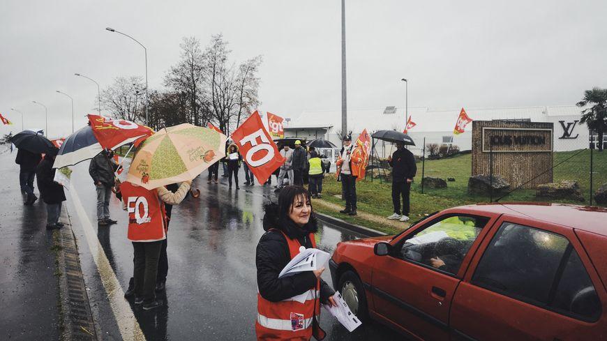 Des manifestants de l'intersyndicale CGT-FO-FSU-Solidaires distribuent des tracts contre la réforme des retraites à l'entrée de la société des ateliers Louis Vuitton