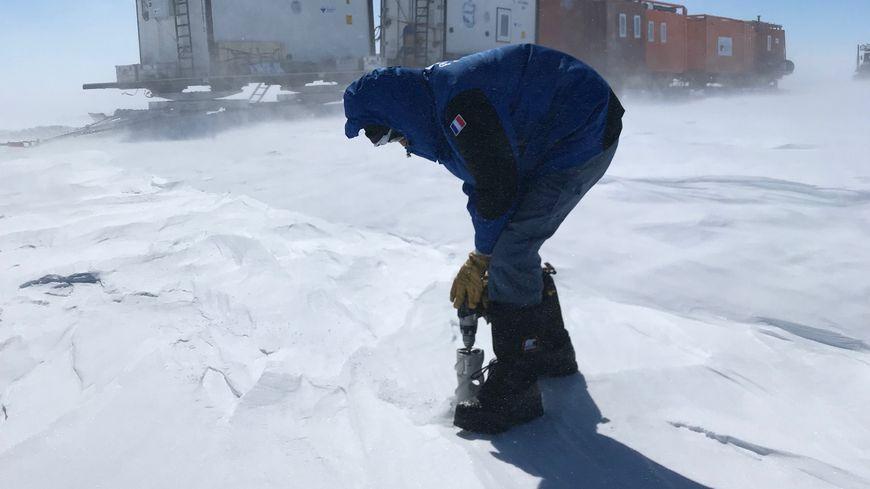 Extraction d'une carotte de glace, avec en arrière plan les caisses isothermes servant au transport de la glace