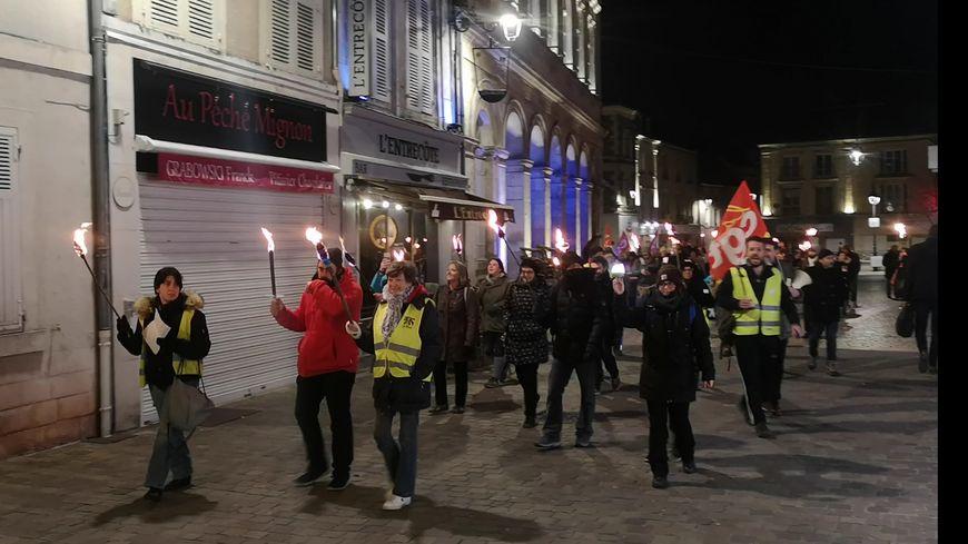 Des manifestants contre la réforme des retraites défilent une torche à la main dans les rues de Châteauroux, jeudi 23 janvier 2020.