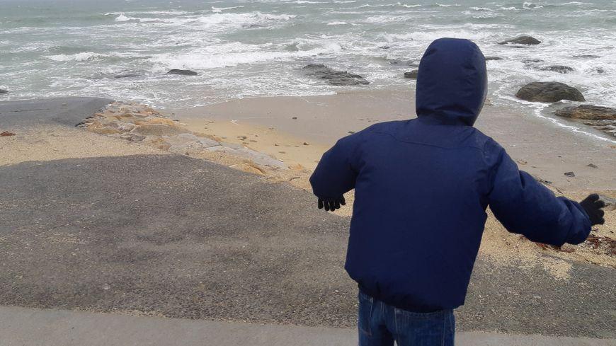 Enfant dans la tempête sur une plage. (Illustration).