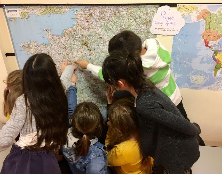 Sur la carte de France et sur le planisphère, des dizaines de gommettes pour représenter les origines des cartes postales