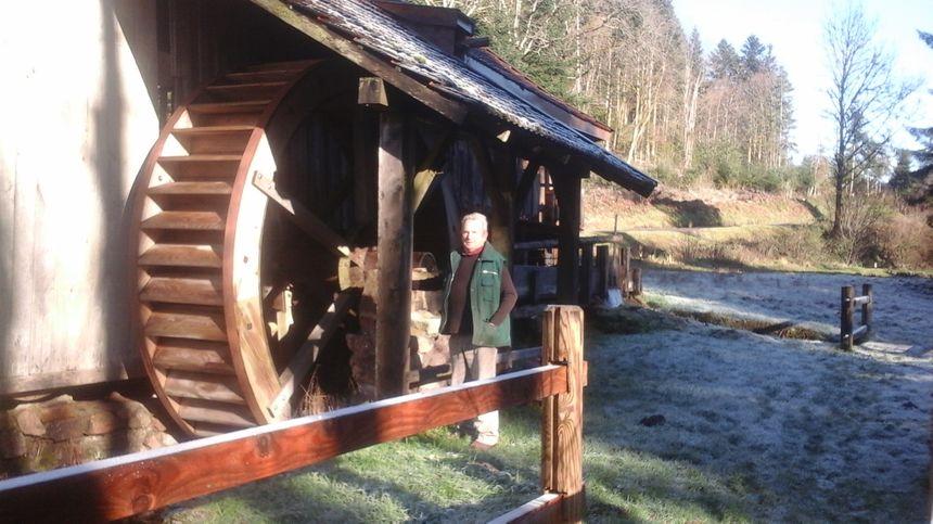 Georges Tuaillon devant la roue qu'il a retapée avec des copains, élément indispensable au mécanisme de cette scierie à haut-fer