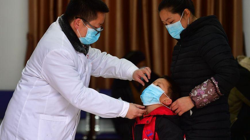 Un membre du corps médical montre comment utiliser les masques dans un village du district de Wuying, en Chine.
