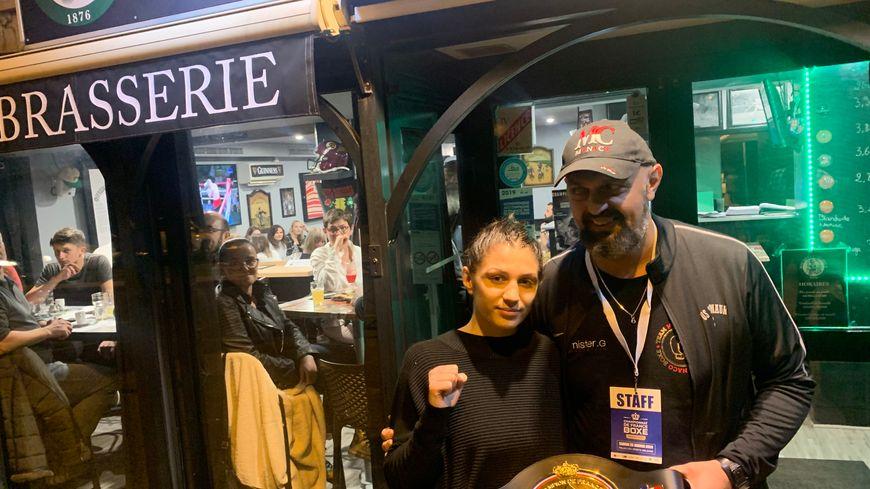 Victoire Piteau avec son père Sébastien pose fièrement avec sa ceinture devant le pub de son père