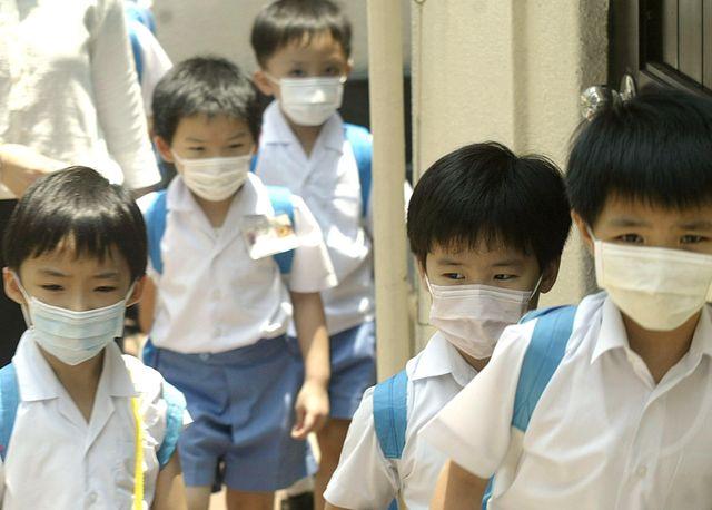 Des écoliers hongkongais portant des masques, en juillet 2003.