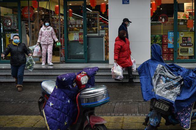 Des habitants de Wuhan quittent un supermarché avec de sacs remplis à ras-bord.