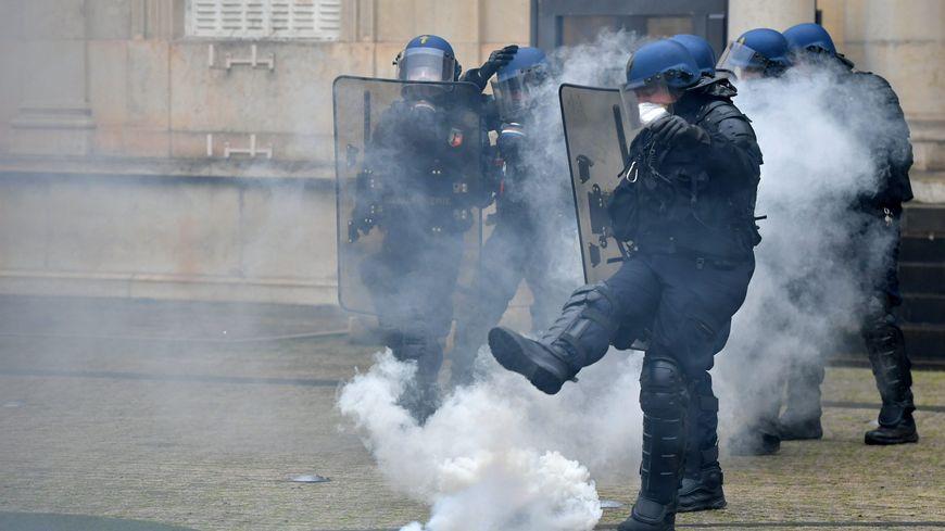 Un policier refoule une grenade.