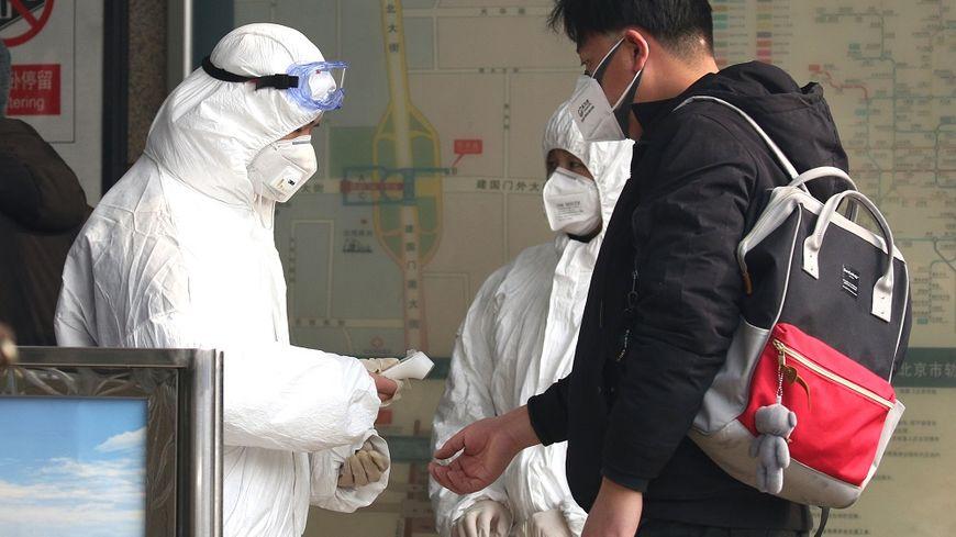 Des employés en combinaison contrôlent la température des passagers à l'entrée d'une station de métro, à Pékin, en Chine.