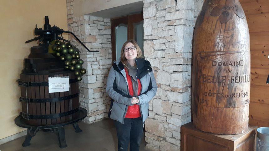 """Céline Meunier devant les objets représentant la Cave Particulière de Vénéjan le domaine de"""" Belle Feuille """"dans le hall d'exposition"""