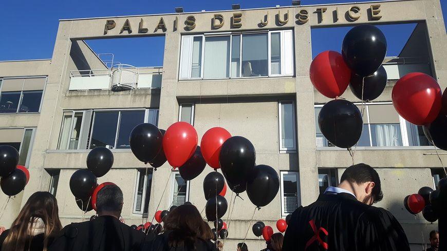 Une haie d'avocats en rouge et noir dans l'enceinte du Palais de justice