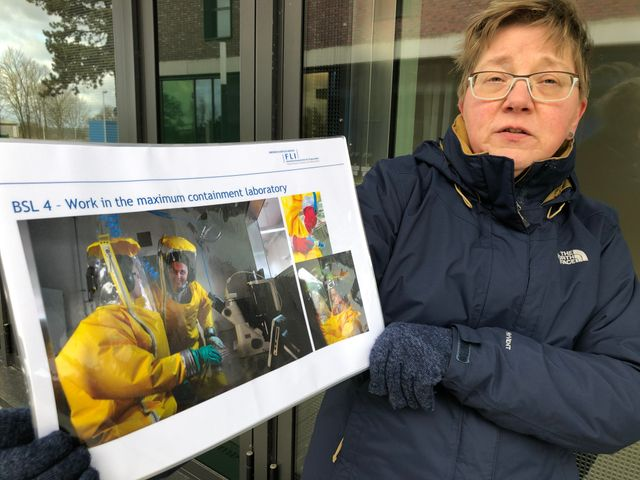 Elke Reinking, biologiste et chargée de la communication de l'Institut, montre les tenues nécessaires pour travailler dans la zone la plus dangereuse