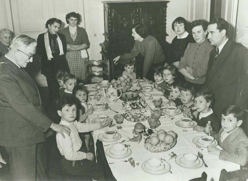 Hubert Védrine enfant, au fond devant le buffet avec sa maman Suzanne lors d' un goûter chez les Mitterrand rue Guynemer à Paris, dans les années 50.