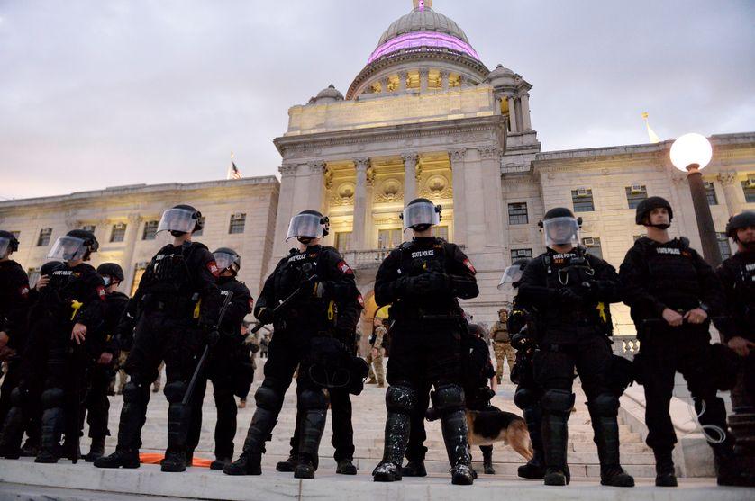 """Des policiers et des militaires font face aux manfestants du mouvement """"Black Live Matter"""" le 5 juin à Rhode Island, Usa."""