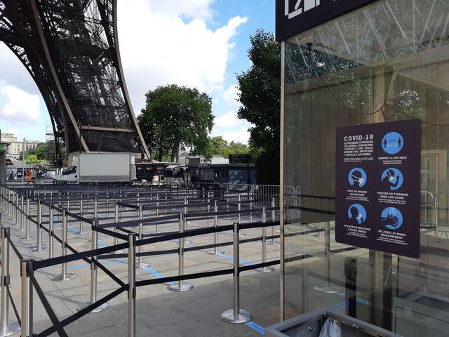 Nouveaux panneaux de rappel des mesures barrières à l'entrée du pilier est de la Tour Eiffel