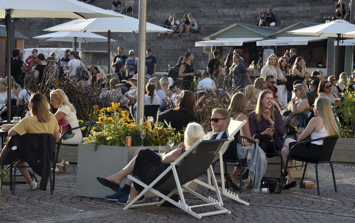 Des habitants d'Helsinki profite du soleil sans porter de masque, le gouvernement ne l'impose pas