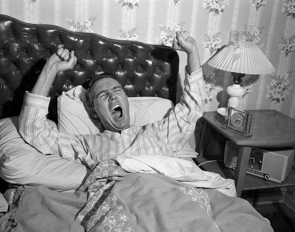 Homme baillant dans son lit