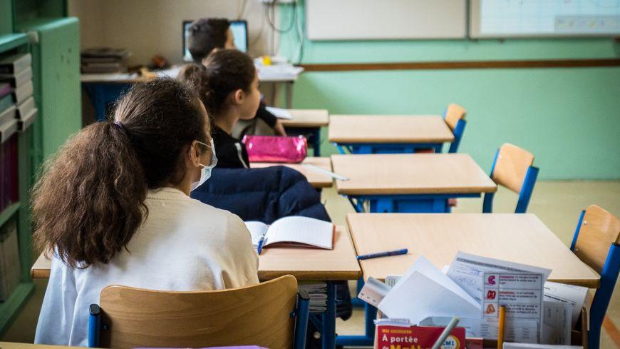 Dans une salle de classe d'une école de Vesoul (Haute-Saône), des tables vides sont placées à côté des élèves afin de garantir le respect de la distanciation physique.