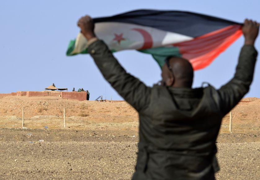 Un combattant sahraoui agite un drapeau du Front Polisario devant un poste marocain sur le mur de sable qui partage le Sahara occidental.