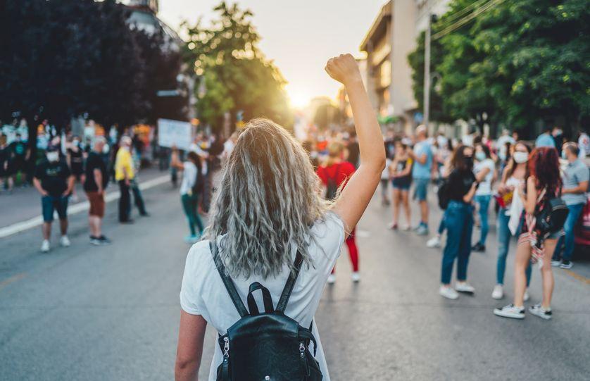 Jeune manifestante levant son poing vers le haut