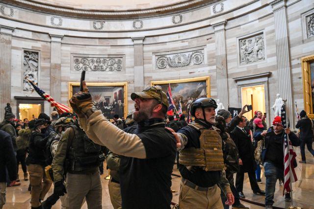Des partisans pro-Trump armés, se prennent en photo dans la rotonde du Capitole