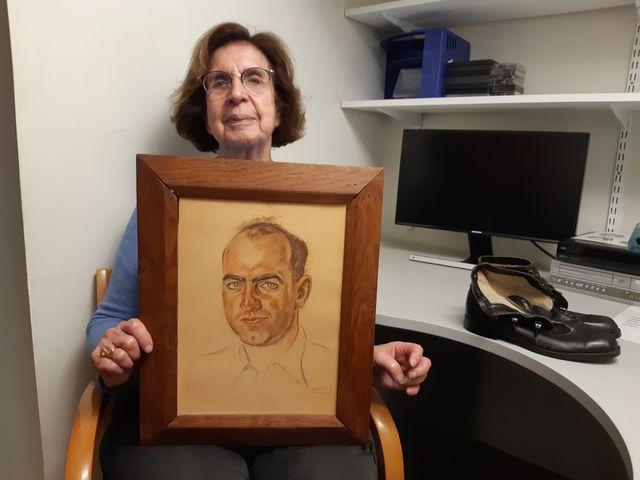 Liliane Ryszfeld tient le portrait de son père, arrêté le 14 mai 1941 et mort à Auschwitz