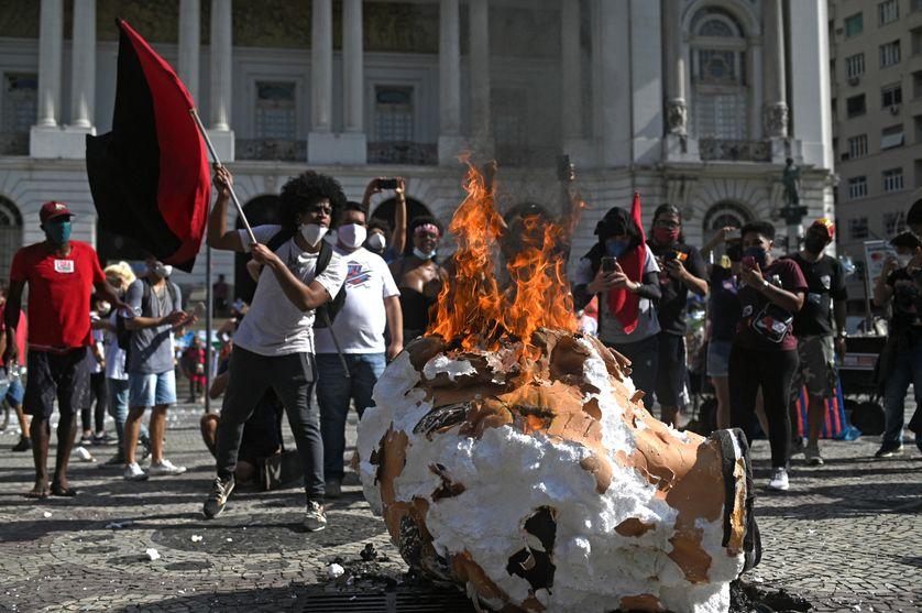 Des manifestants mettent le feu à un mannequin représentant le président brésilien Jair Bolsonaro lors d'une manifestation contre sa gestion de la pandémie COVID-19 à Rio de Janeiro, le 29 mai 2021.