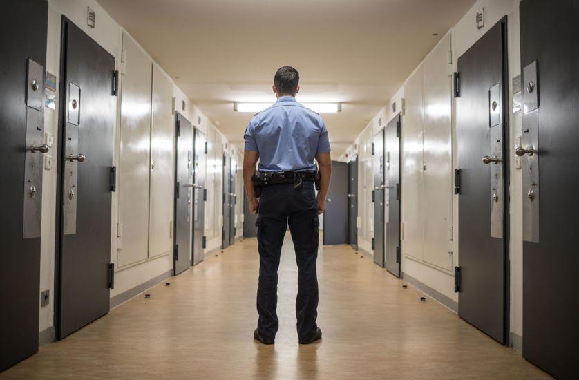 Un gardien dans une allée entre les portes des cellules d'isolement du pénitencier de Francfort I, à Francfort-sur-le-Main, Allemagne, le 8 août 2017